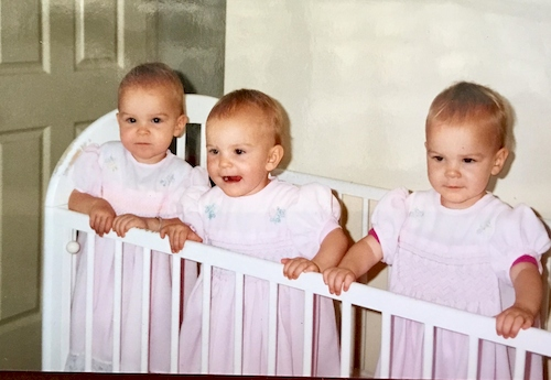 identical triplet girls in cot
